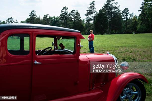 Randy Kinrey a supporter of US President Donald Trump poses with his classic car May 19 2017 in Level Cross North Carolina While some observers see...