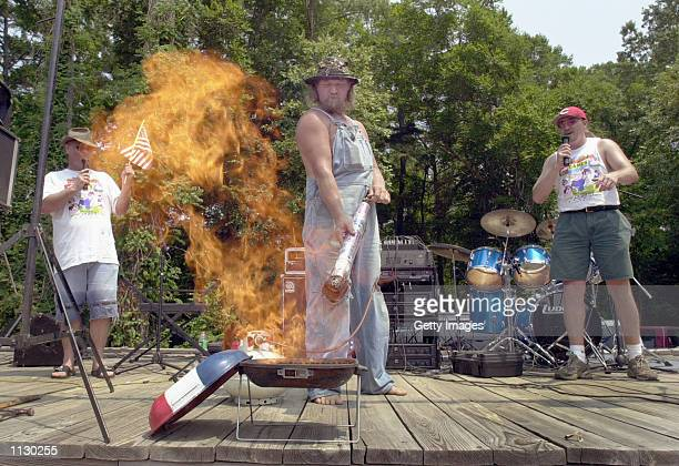 Randy 'LBow' Tidwell lights the barbeque pit with his propane torch to mark the opening of the Seventh Annual Summer Redneck Games July 6 2002 in...