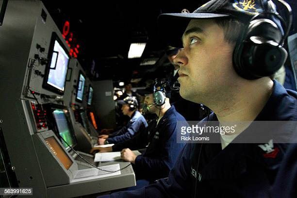 Randy Loewen a sensor operator in the sonar room of the destroyer USS Momsen inspects the monitors for signs of a submarine or marine mammals during...