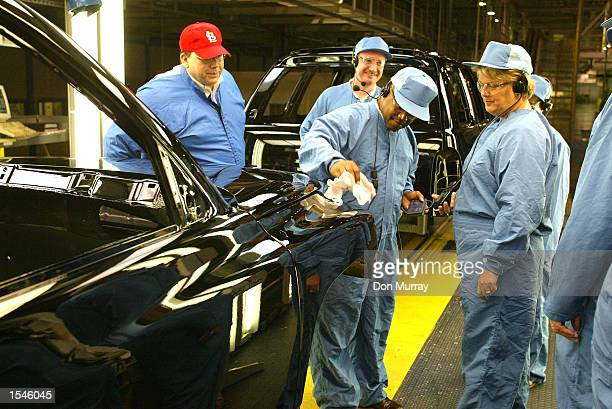 Randy Mielnick DuPont Business Manager Tom Webster Chrysler Environmental Specialist watch as Marion Boone Chrysler Paint Manufacturing Manager shows...