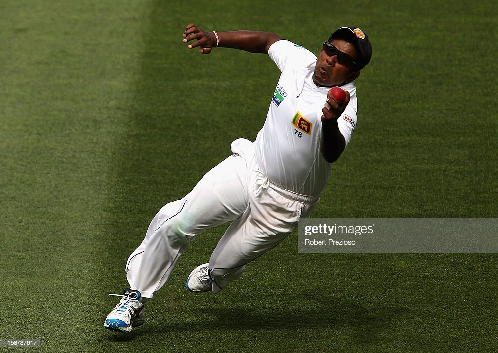 Rangana Herath of Sri Lanka takes a catch to dismiss Michael Hussey of Australia off the bowling of Tillakaratne Dilshan of Sri Lanka during day two of the Second Test match between Australia and Sri Lanka at Melbourne Cricket Ground on December 27, 2012 in Melbourne, Australia.