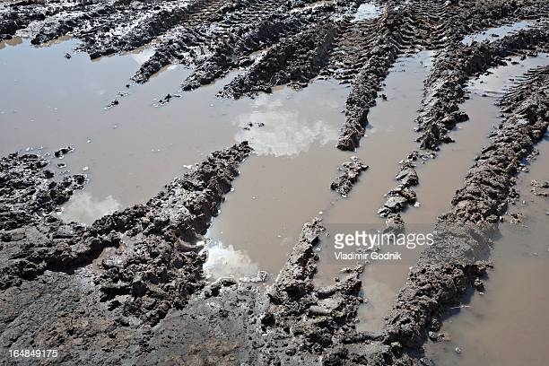 Range of construction vehicle tracks across a puddle on construction site