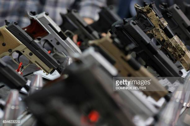 A range of pistols is seen on display at a National Rifle Association outdoor sports trade show on February 10 2017 in Harrisburg Pennsylvania The...