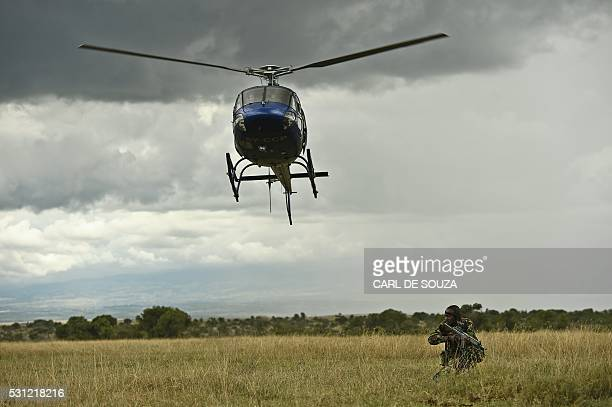 A ranger from Ol Pejeta Sanctuary's stands next to a flying helicopter holding a riffle as the tactical anti poaching response team carry out a drill...