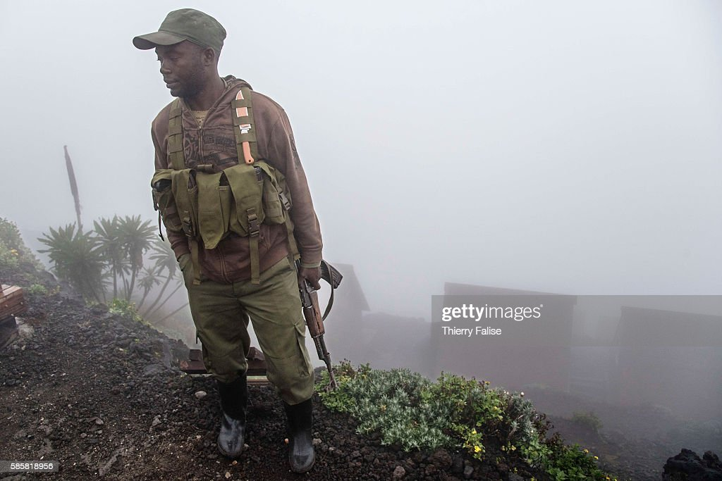 A ranger in the morning mist stands near huts for visitors on the top of Mount Nyiragongo The Nyiragongo is an active stratovolcano with an elevation...