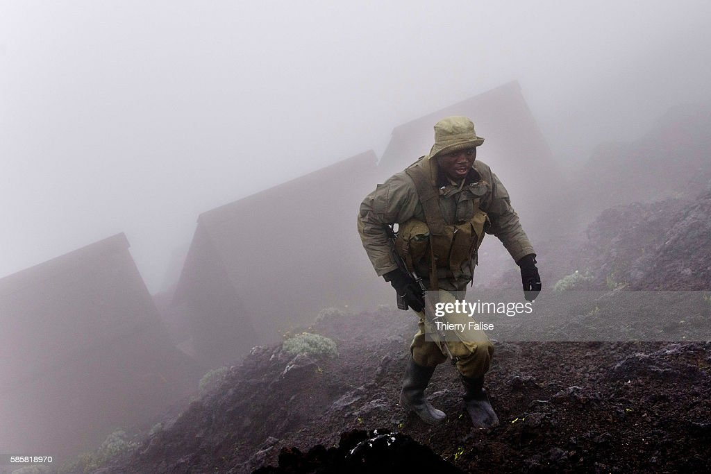 A ranger in the morning mist walks past huts for visitors on the top of Mount Nyiragongo The Nyiragongo is an active stratovolcano with an elevation...