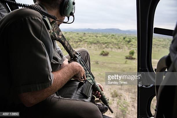 Ranger Rob Thompson searches from a helicopter for a poacher on the run on November 7 2014 at the Kruger National Park South Africa The suspected...