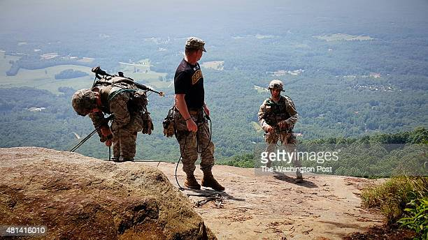 Ranger students left and right reach the top of a 150cliff they climbed near the top of Mount Yonah in Georgia as part of Ranger School's Mountain...