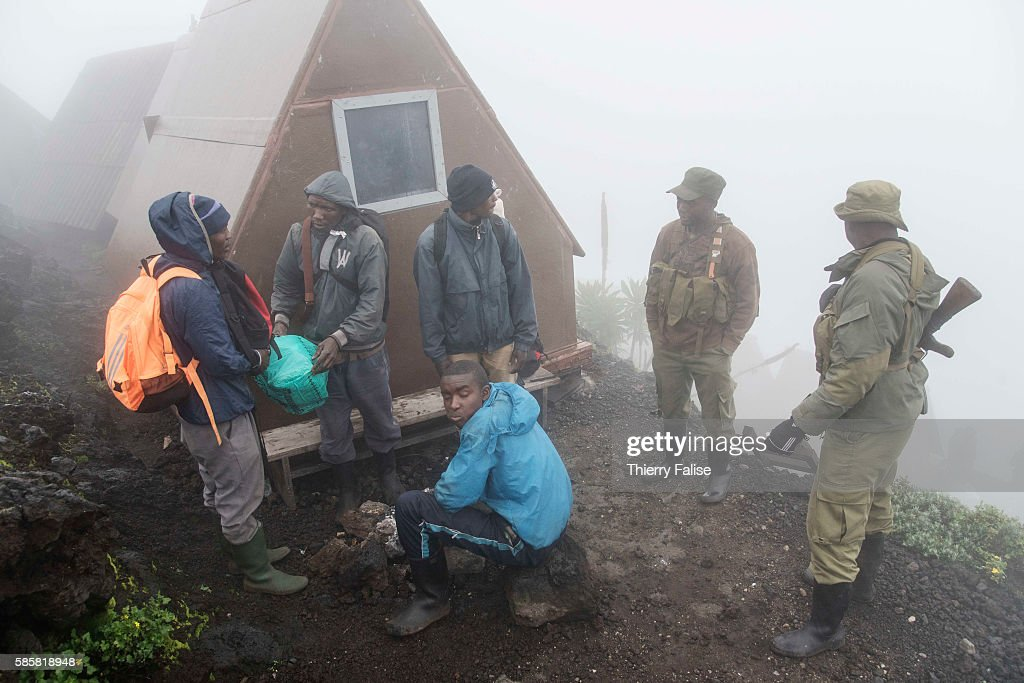 Rangers and porters in the morning mist are getting ready for the walk down Mount Nyiragongo The Nyiragongo is an active stratovolcano with an...