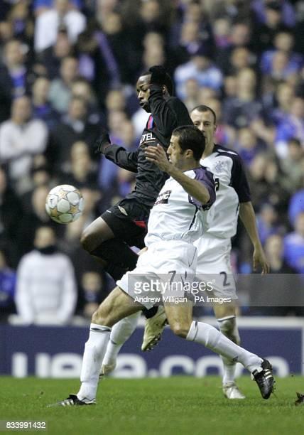 Rangers' Brahim Hemdani and Olympique Lyonnais' Sidney Govou battle for the ball