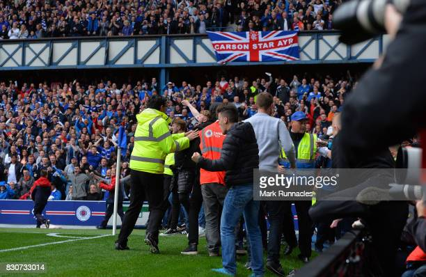 Rangers fans pour out of the stand onto the pitch as Alfredo Morelos of Rangers celebrates scoring the opening goal of the game with his team mates...