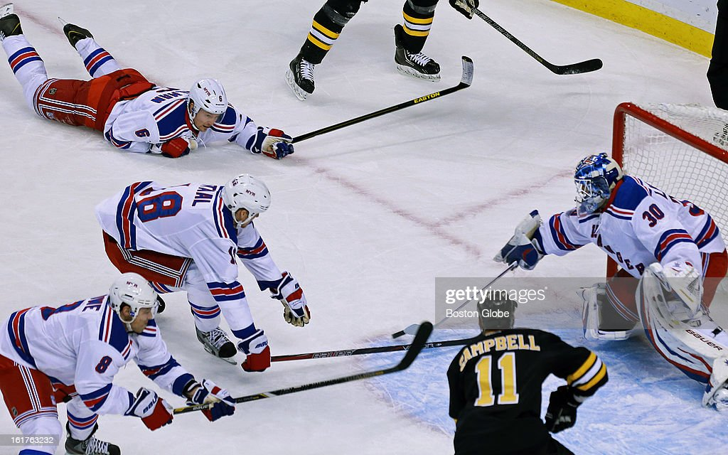 Rangers goalie Henrik Lundqvist gets some help from teammates, top to bottom, Anton Stralman, Mark Staal and Darroll Powe as they make sure that the Bruins' Gregory Campbell (#11) can't pounce on a loose puck in front of the net during first period action as the Boston Bruins hosted the New York Rangers in an NHL regular season hockey game at the TD Garden.