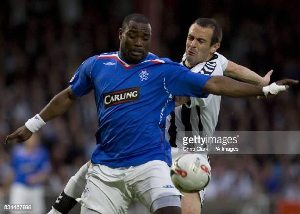 Rangers' JeanClaude Darcheville battles with St Mirren's John Potter during the Clydesdale Bank Premier League match at St Mirren Park Paisley