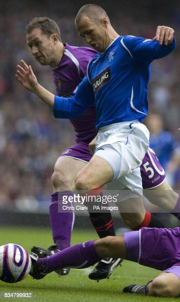Rangers' Kenny Miller is tackled by Frazer Wright and James Fowler of Kilmarnock during the Clydesdale Bank Scottish Premier League match at Ibrox...