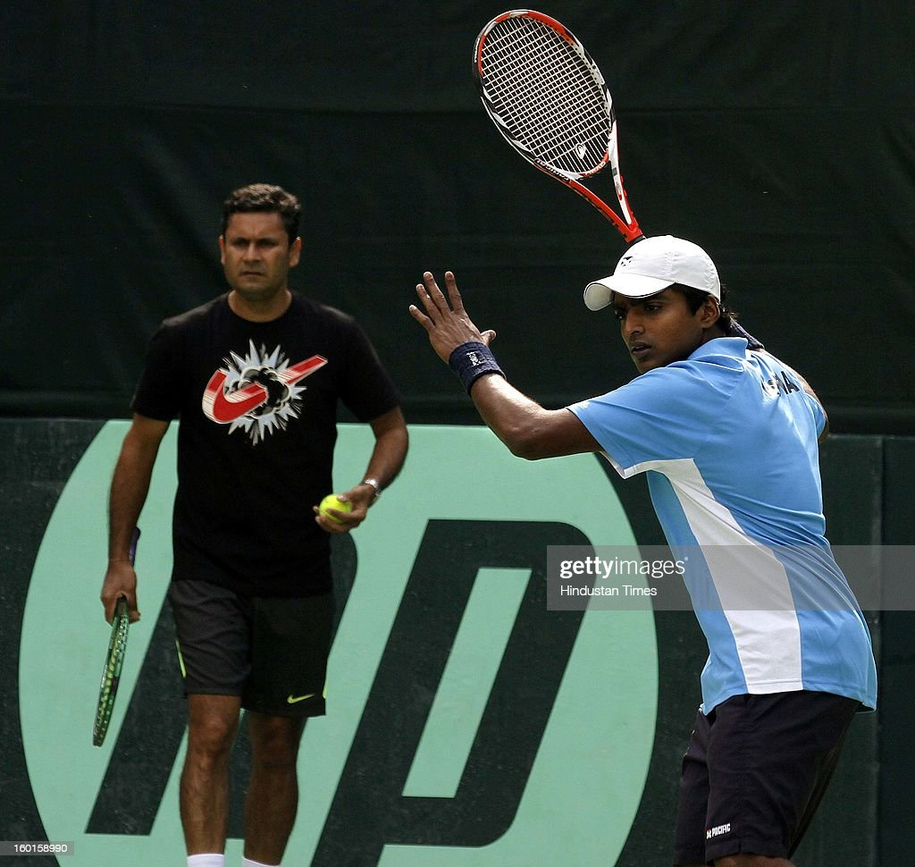 V M Ranjeeth member of India Davis cup team plays a shot as coach Zeeshan Ali looks on during practice session at Delhi Lawn Tennis Association on January 27, 2013 in New Delhi, India.