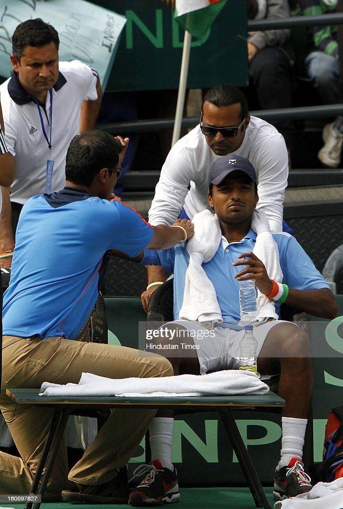 VM Ranjeeth of India gets some massage during Davis cup reverse single match against Jeong Suk Young of Korea as Leander Paes looks on at Delhi Lawn Tennis Association stadium on February 3, 2013 in New Delhi, India.