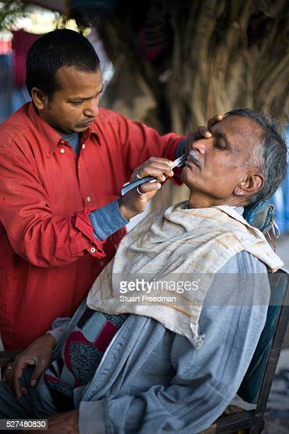 Ranjit Sharma 59 has his haircut by a roadside barber outside the Fatepuri night shelter for the homeless before going to work Originally from...
