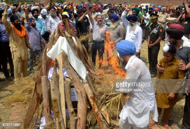 Ranjit Singh and Sahildeep Singh the brother and son of Indian Army soldier Paramjeet Singh light his funeral pyre in Vein Pein village some 45 kms...