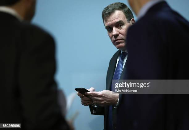 Ranking member of the Senate Select Intelligence Committee Sen Mark Warner checks his phone prior to the start of a hearing held by the Senate Select...
