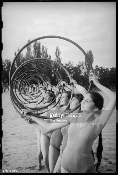 Ranks of gymnast girls with hoops at stadium Uzbekistan circa 1940