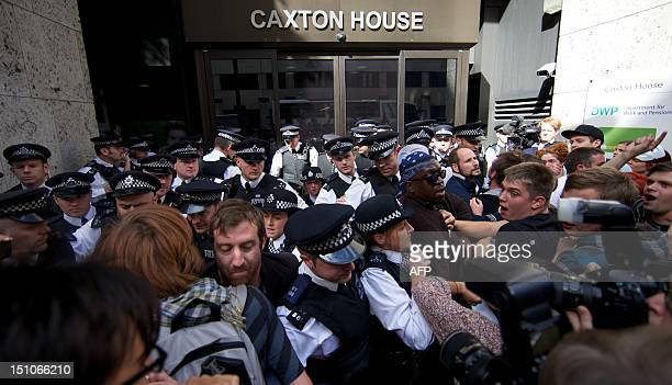 Ranks of police officers disperse protesters against multinational IT firm and Paralympics sponsor Atos from outside the offices of the Department of...