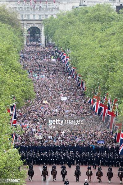 Ranks of police officiers lead crowds of people marching along the Mall toward Buckingham Palace to see Britain's Queen Elizabeth IIn and other...