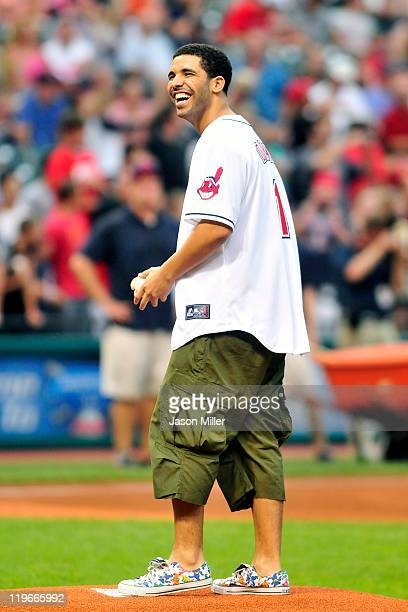 Rap artist Drake laughs as he throws out the ceremonial first pitch before the game between the Cleveland Indians and the Chicago White Sox at...