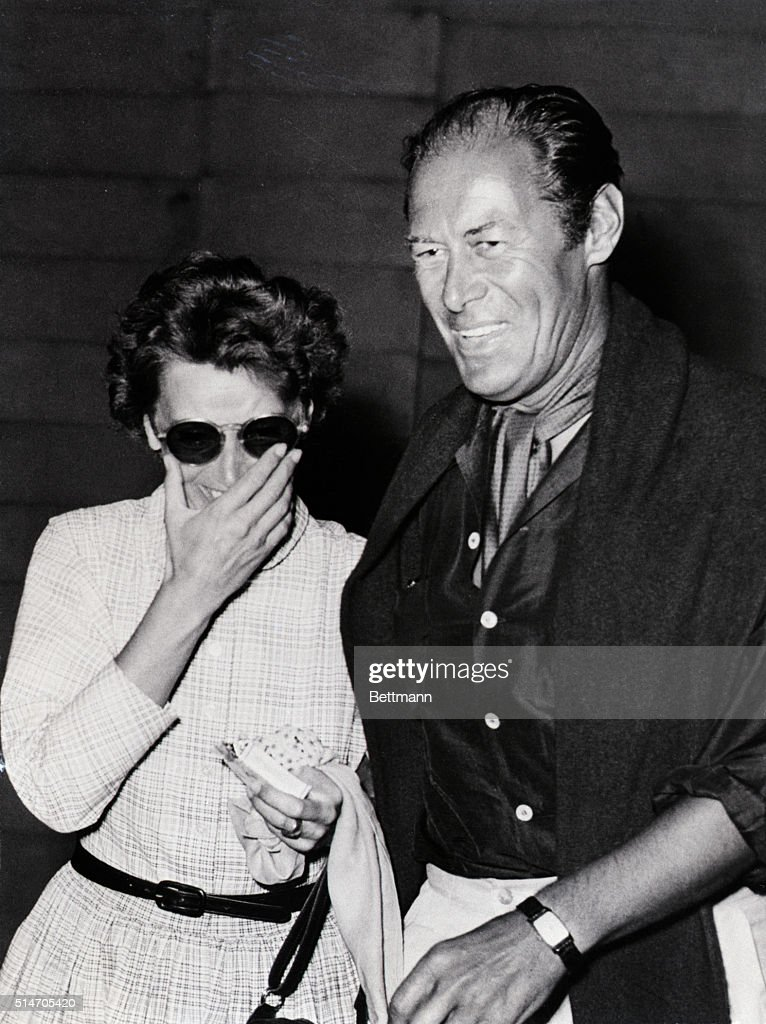 The price of fame: Actor Rex Harrison and film star Greta Garbo discover that there is no escape possible from the persistent cameraman who catches them as they enter a restaurant in Rapallo. At left, the fabulous Garbo covers her smile as Rex beams in submission to the photographer. Earlier, the camera caught Harrison giving the hand signal to 'stop' as he escorted the Swedish-born actress up the stairs of the restaurant. At this point it is cleraly seen that the lady is amused by the whole thing.