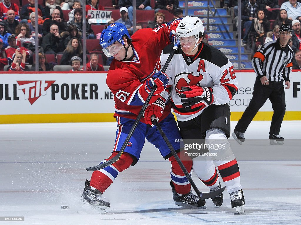 Raphael Diaz #61 of the Montreal Canadiens battles for a loose puck with Patrik Elias #26 of the New Jersey Devils during the NHL game on January 27, 2013 at the Bell Centre in Montreal, Quebec, Canada.