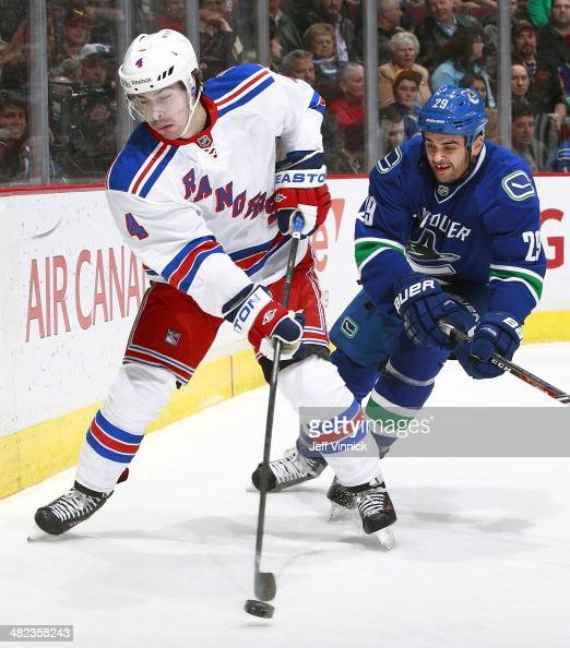 Raphael Diaz of the New York Rangers and Tom Sestito of the Vancouver Canucks battle for the puck during their NHL game at Rogers Arena April 1 2014...