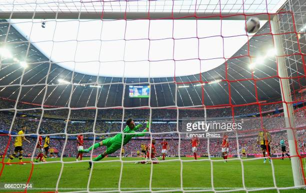 Raphael Guerreiro of Borussia Dortmund scores his sides first goal past Sven Ulreich of Bayern Muenchen during the Bundesliga match between Bayern...