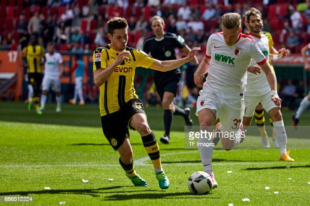Raphael Guerreiro of Dortmund and Philipp Max of Augsburg battle for the ball during the Bundesliga match between FC Augsburg and Borussia Dortmund...