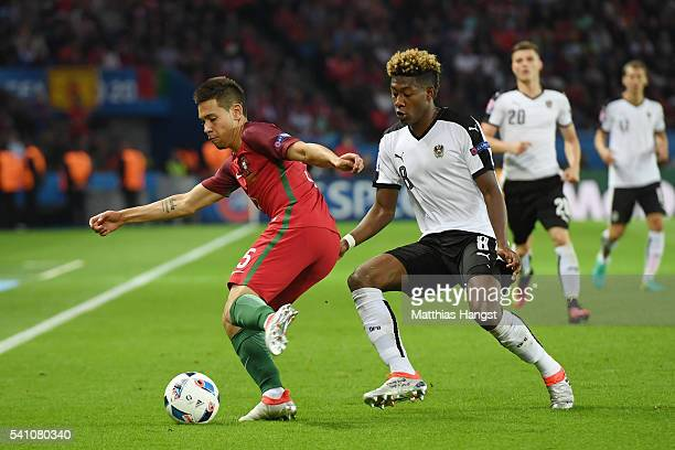 Raphael Guerreiro of Portugal and David Alaba of Austria compete for the ball during the UEFA EURO 2016 Group F match between Portugal and Austria at...
