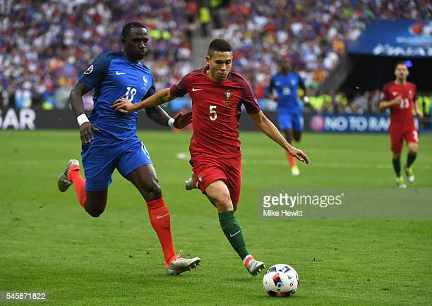 Raphael Guerreiro of Portugal controls the ball under pressure of Moussa Sissoko of France during the UEFA EURO 2016 Final match between Portugal and...