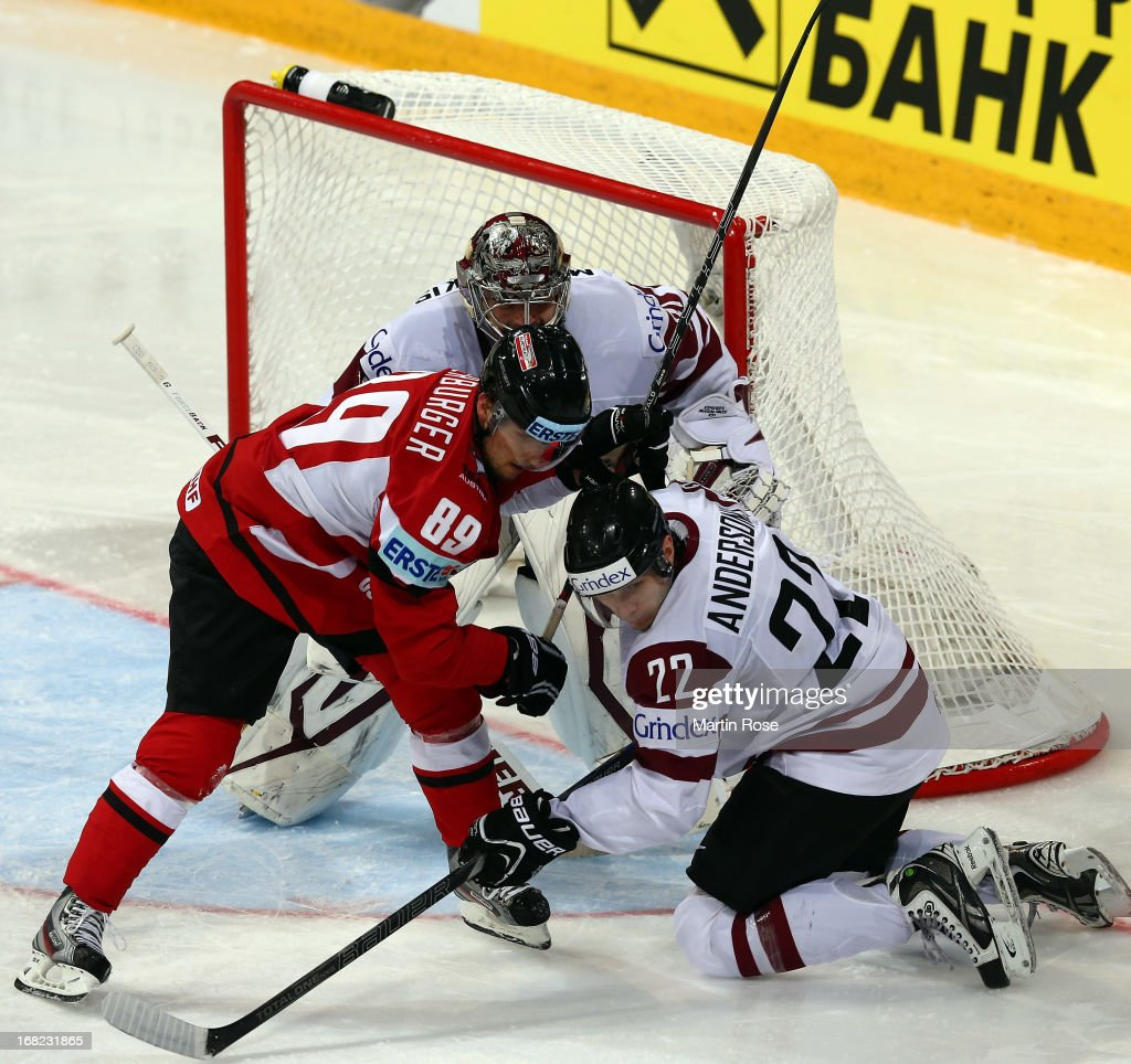 Raphael Herburger (L) of Austria and Janis Andersons (R) of Latvia battle for the puck during the IIHF World Championship group H match between Austria and Latvia at Hartwall Areena on May 7, 2013 in Helsinki, Finland.