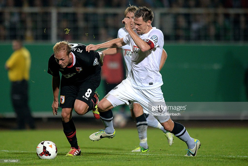 Raphael Holzhaeuser of Augsburg and Stefan Kuehne of Muenster battle for the ball during DFB Cup second round match between Preussen Muenster and FC Augsburg at Preussenstadion on September 24, 2013 in Muenster, Germany.