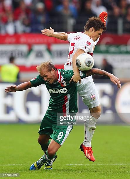Raphael Holzhauser of Augsburg is challenged by Gotoku Sakai of Stuttgart during the Bundesliga match between FC Augsburg and VfB Stuttgart at SGL...