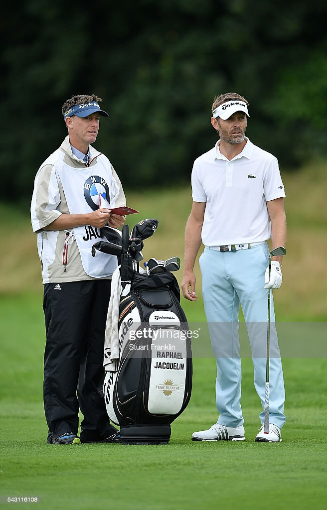 Raphael Jacquelin of France looks on with his caddie during the rain delayed third round of the BMW International Open at Gut Larchenhof on June 26, 2016 in Cologne, Germany.