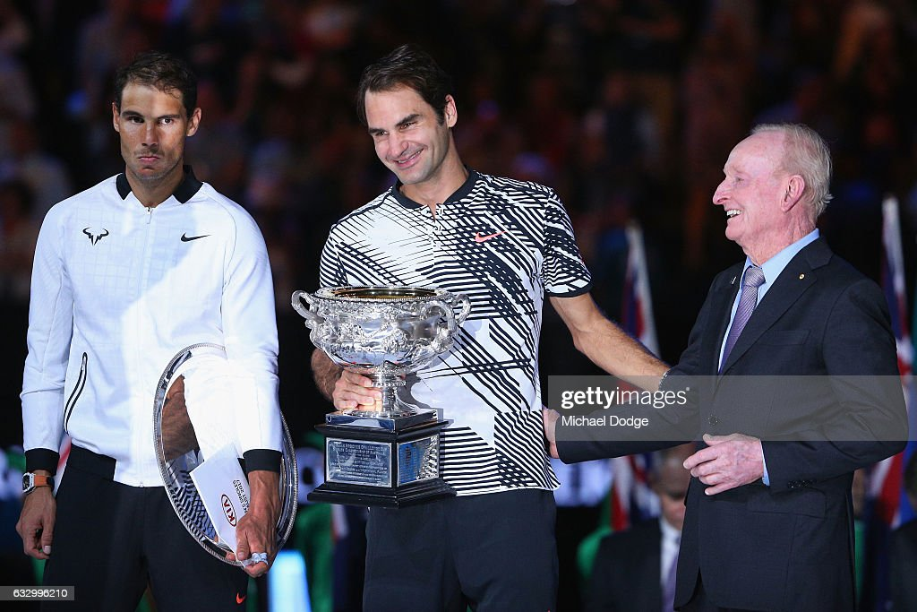 Raphael Nadal of Spain (L) reacts as Australian Tennis legend Rod Laver hugs Roger Federer of Switzerland who celebrates with the Trophy after winning in the Men's Final match against on day 14 of the 2017 Australian Open at Melbourne Park on January 29, 2017 in Melbourne, Australia.