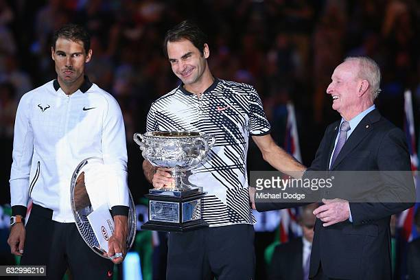 Raphael Nadal of Spain reacts as Australian Tennis legend Rod Laver hugs Roger Federer of Switzerland who celebrates with the Trophy after winning in...
