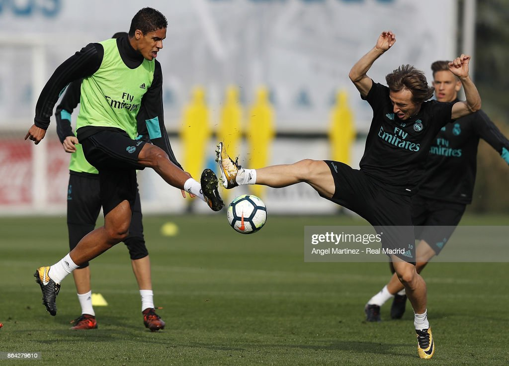 Raphael Varane (L) and Luka Modric of Real Madrid in action during a training session at Valdebebas training ground on October 21, 2017 in Madrid, Spain.