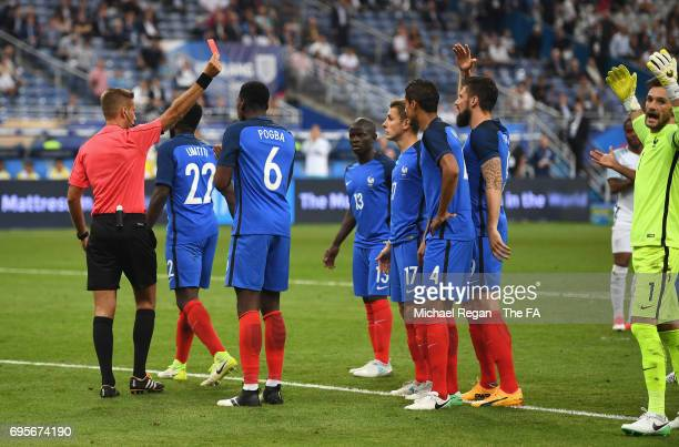 Raphael Varane of France is shown a red card and is sent off by referee Davide Massa during the International Friendly match between France and...
