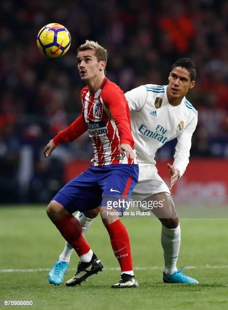 Raphael Varane of Real Madrid and Antoine Griezmann of Atletico de Madrid compete for the ball during the La Liga match between Atletico Madrid and...