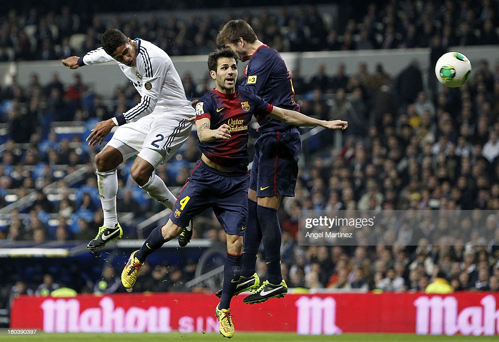 Raphael Varane of Real Madrid heads the ball to score past Cesc Fabregas (C) and <a gi-track='captionPersonalityLinkClicked' href=/galleries/search?phrase=Gerard+Pique&family=editorial&specificpeople=227191 ng-click='$event.stopPropagation()'>Gerard Pique</a> of Barcelona during the Copa del Rey Semi-Final first leg match between Real Madrid CF and FC Barcelona at Estadio Santiago Bernabeu on January 30, 2013 in Madrid, Spain.