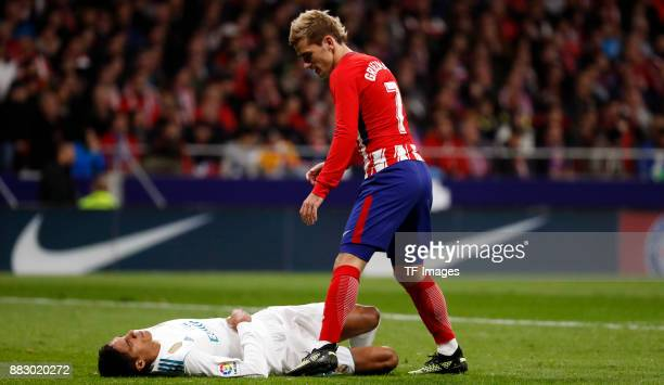 Raphael Varane of Real Madrid on the ground and Antoine Griezmann of Atletico de Madrid is helping during a match between Atletico Madrid and Real...