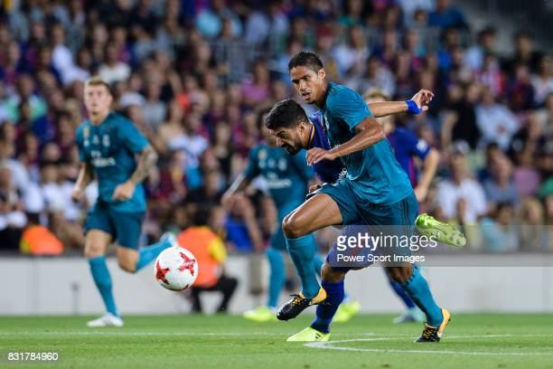 Raphael Varane of Real Madrid plays against Luis Suarez of FC Barcelona during the Supercopa de Espana Final 1st Leg match between FC Barcelona and...