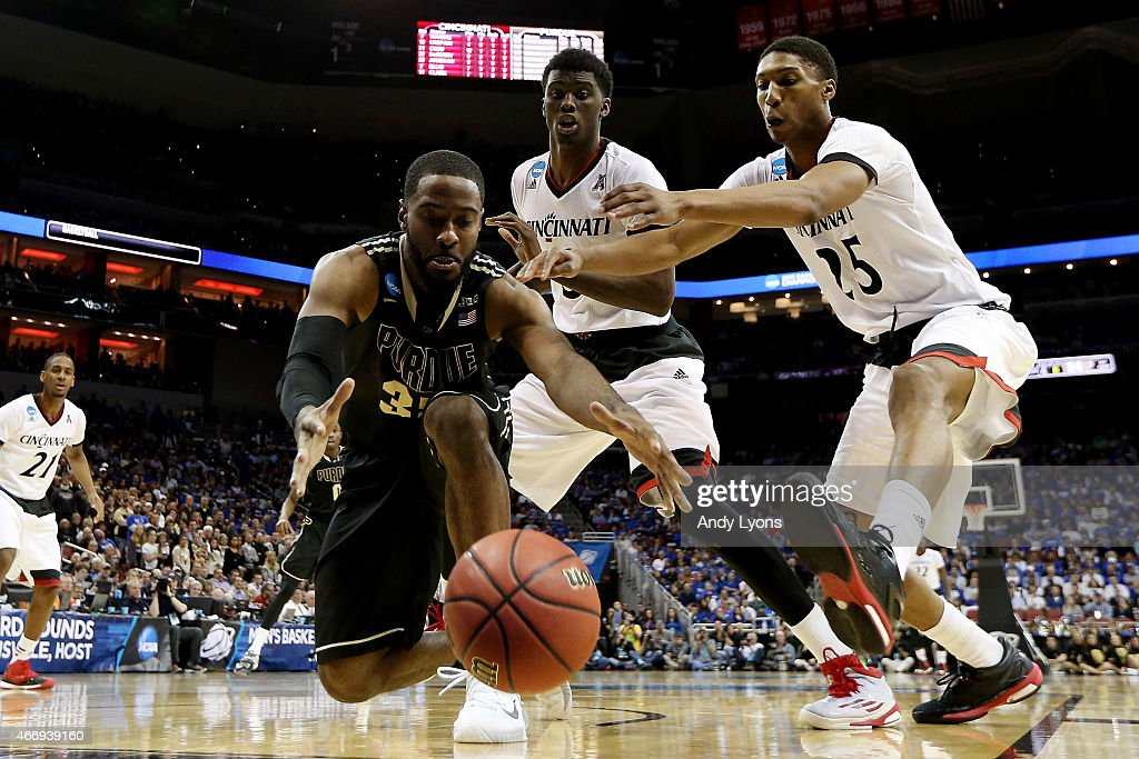 Rapheal Davis of the Purdue Boilermakers and Kevin Johnson of the Cincinnati Bearcats go for a loose ball during the second round of the 2015 NCAA...