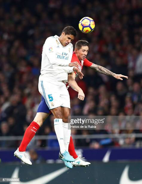 Rapheal Varane of Real Madrid and Fernando Torres of Atletico de Madrid compete for the ball during the La Liga match between Atletico Madrid and...