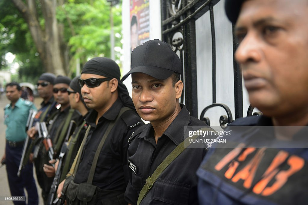 Rapid Action Battalion (RAB) personnel stand guard in front of the high court in Dhaka on September 17, 2013, after a verdict was delivered against Abdul Quader Molla, the fourth-highest leader of the Jamaat-e-Islami party. Bangladesh's top court sentenced to death a senior Islamist opposition official for murder during the 1971 liberation war against Pakistan. Abdul Quader Molla is the first politician to be found guilty by the country's Supreme Court after it rejected an appeal to acquit him of all charges. AFP PHOTO/Munir uz ZAMAN