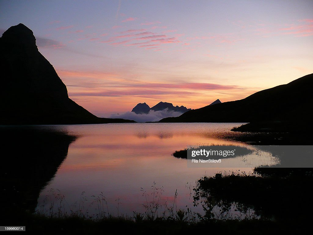 CONTENT] Rappensee mountain lake in the bavarian part of the Allgäu Alps. Photo taken after sunset, the sky is reflecting on the lake and there are mountains silhouettes around and on the horizon.